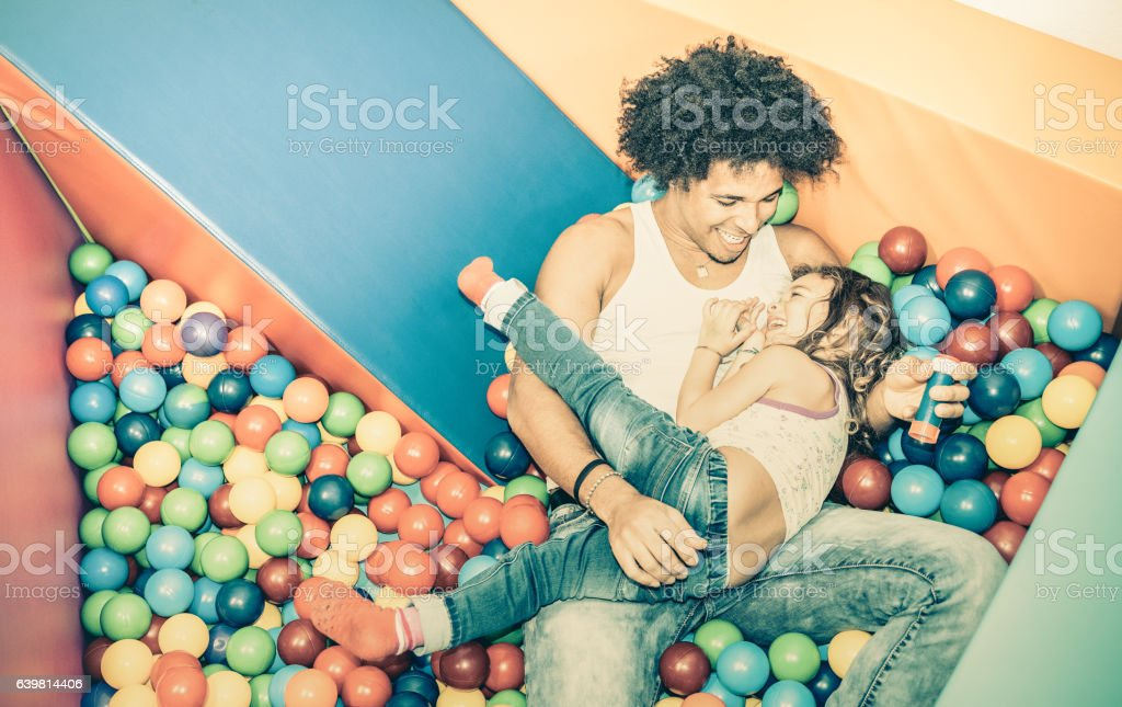 Latin dad playing with funny daughter on ball pit pool stock photo