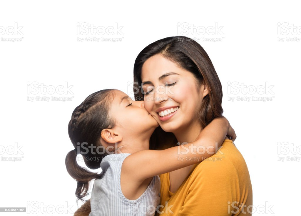 Latin daughter kissing mommy stock photo