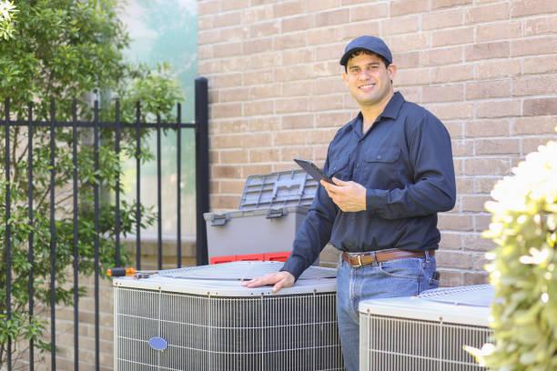 Latin descent, blue collar air conditioner repairman at work. stock photo