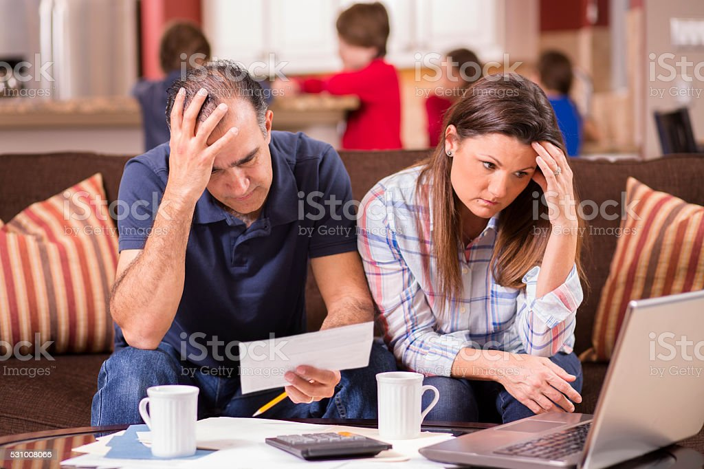 Latin descent man and woman struggle to pay their monthly bills. They...
