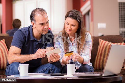 istock Latin descent couple paying monthly bills at home. 513822304