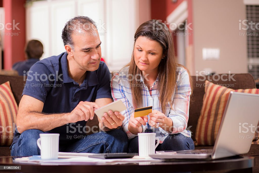 Latin descent couple paying monthly bills at home. stock photo