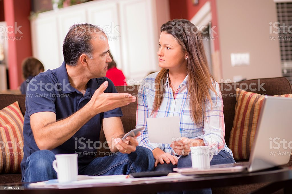 Latin descent man and woman argue while paying their monthly bills....