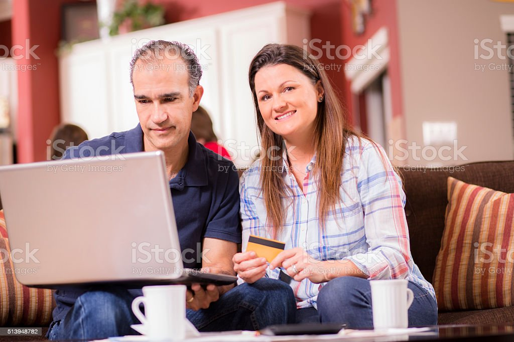 Latin descent man and woman work together to pay their monthly bills...