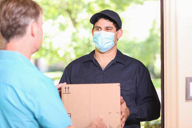 Latin descent delivery man with box arrives at customer home. Latin descent delivery man arrives at customer's front door with cardboard box to make a delivery. Mature man greets man at door. He wears a blue uniform, covid mask and holds cardboard box. covid-19 stock pictures, royalty-free photos & images