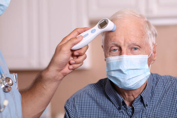 COVID-19: Latin descent doctor and senior adult patient, fever, masks. Latin descent doctor or healthcare worker, consultation with senior adult patient in office, hospital, or clinic setting.  He checks fever of patient with infrared thermometer.  Both wear protective face masks.  Coronavirus, medical exam, consultation. covid-19 stock pictures, royalty-free photos & images