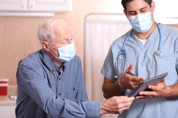COVID-19: Latin descent doctor and senior adult patient, masks. stock photo