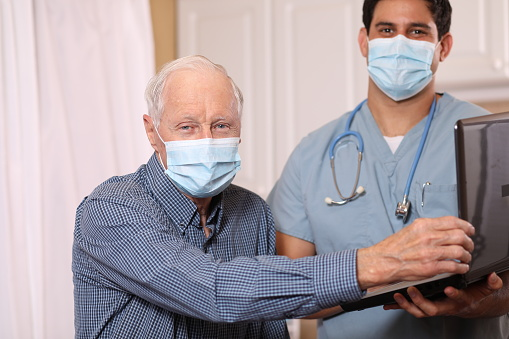 Covid19 Latin Descent Doctor And Senior Adult Patient Masks Stock Photo - Download Image Now
