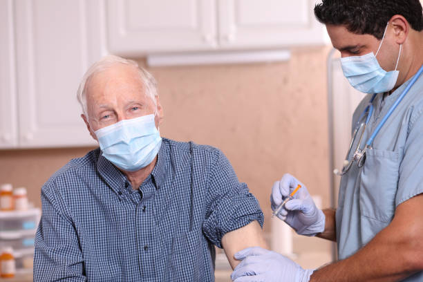 COVID-19: Latin descent doctor and senior adult patient, vaccine, masks. stock photo
