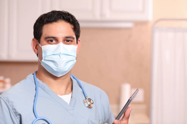 COVID-19: Latin descent doctor or nurse uses digital tablet. Latin descent doctor or healthcare worker uses digital tablet while wearing his protective face mask during work in hospital or clinic setting.  Coronavirus, medical exam, consultation. covid-19 stock pictures, royalty-free photos & images