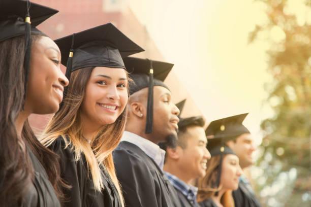 Latin descent female college student graduation on campus. stock photo