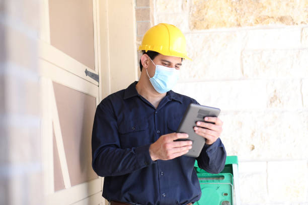 Latin descent man inspects home exterior. Latin descent man inspects home exterior.  He could be a home inspector, insurance adjuster, exterminator or a variety of technician occupations. He holds a digital tablet and wears hard hat and covid mask. covid-19 stock pictures, royalty-free photos & images