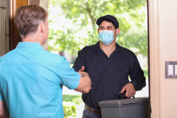 Latin descent repairman, technician makes house call at customer home. Latin descent repairman arrives at customer's front door to make requested home repairs. Mature man greets repairman. He wears a covid mask, blue uniform and holds toolbox as they shake hands. covid-19 stock pictures, royalty-free photos & images