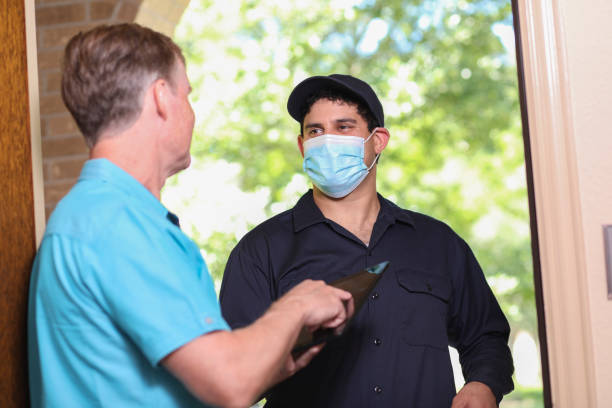 Latin descent repairman, technician makes house call at customer home. Latin descent repairman arrives at customer's front door to make requested home repairs. Mature man greets repairman. He wears a covid mask, blue uniform and holds digital tablet and toolbox. covid-19 stock pictures, royalty-free photos & images
