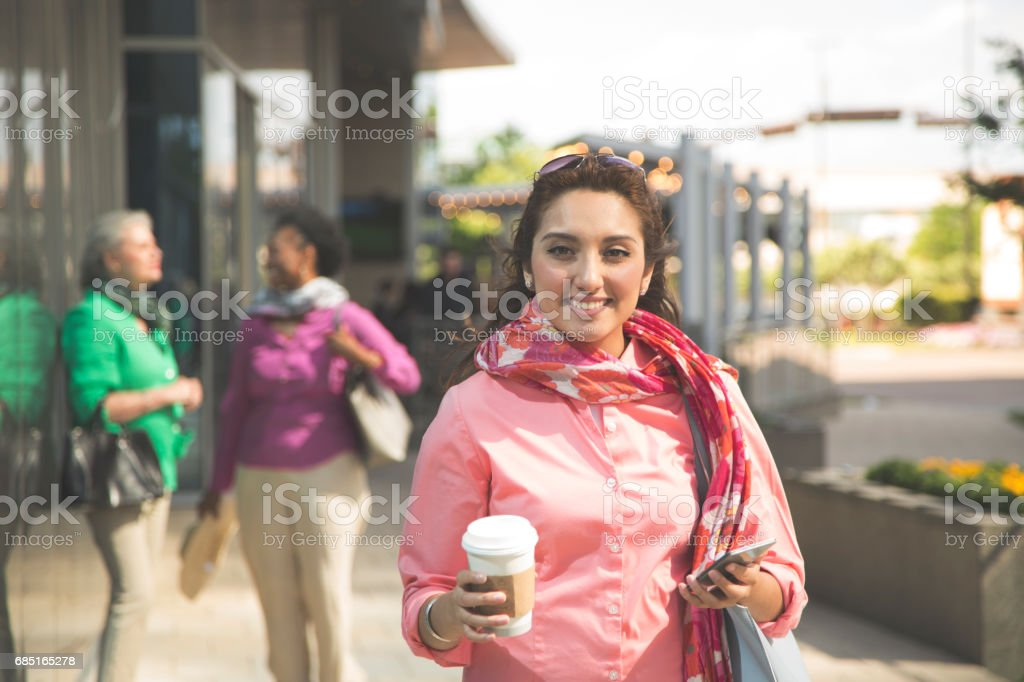 Latin descent woman using cell phone in downtown city area. foto de stock libre de derechos