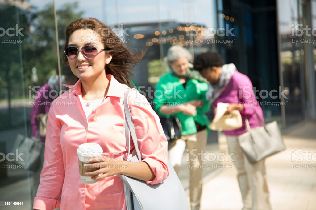 Latin descent woman walking in downtown city area. royalty-free stock photo