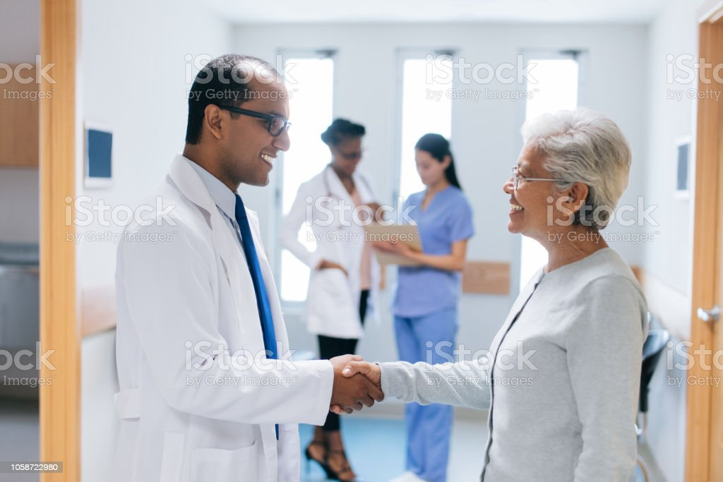 A latin male doctor and a senior female patient standing face to face...
