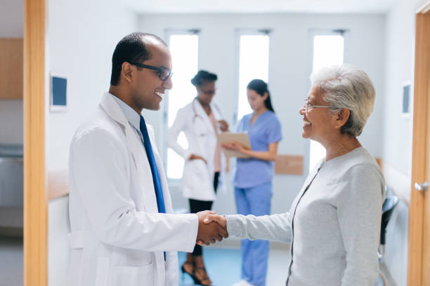 Latin doctor and patient shaking hands in hospital hall A latin male doctor and a senior female patient standing face to face in a hospital hall, shaking hands and smiling at each other. general military rank stock pictures, royalty-free photos & images