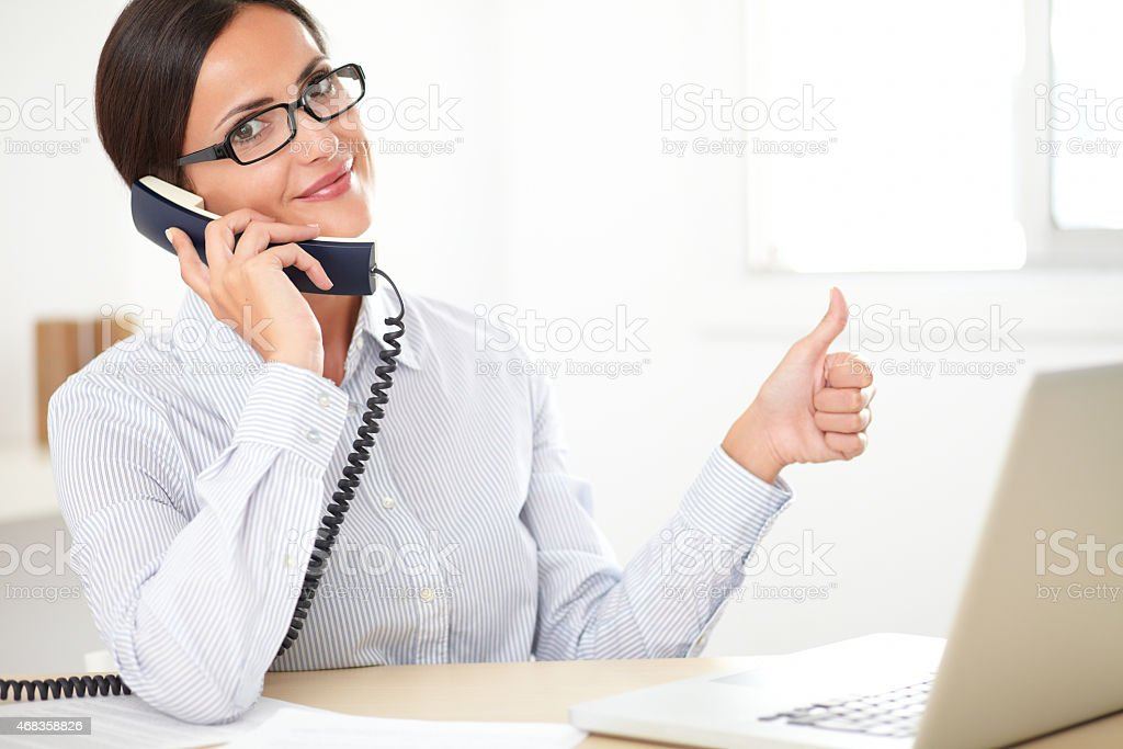 Latin employee happily doing customer service royalty-free stock photo