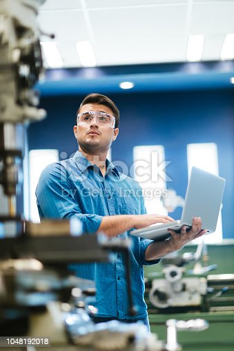 A young hispanic engineering student calibrating the equipment in his shop class with his laptop