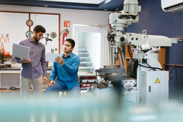 Latin engineers working on tablet and laptop in shop stock photo