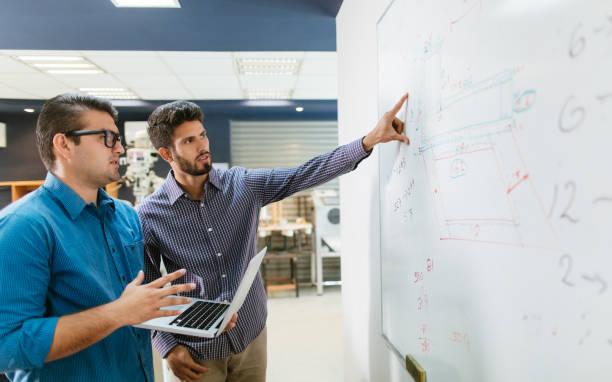 Latin engineers working on whiteboard stock photo