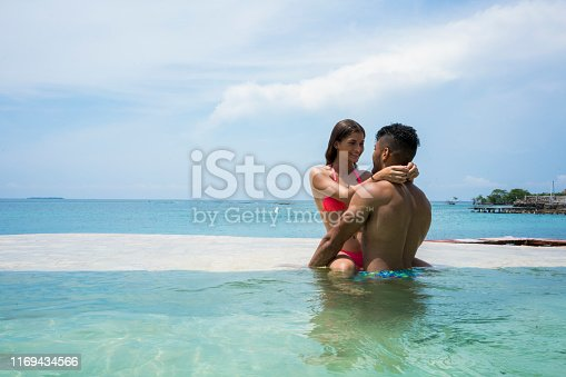 Latin ethnicity couple hugging inside a pool, in the middle of an island with the sea in the background.