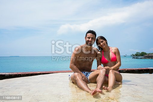 Latin ethnicity couple sitting in a pool with the sea in the background looking at the camera while smiling.
