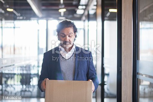 Latin executive man of approximately 50 years dressed in blue suit gray coat and white shirt walks through the corridors of the company where he works with a cardboard box where he carries his personal things in his hands which looks sadly since it was fired from his work half body picture