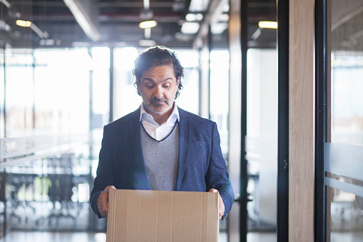 1048789678 istock photo Latin executive man looks at the cardboard box he holds in his hands sadly 1181092210