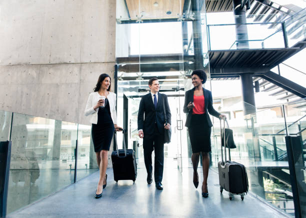 Latin executives walking with suitcases and hand luggage Cheerful multi-ethnic young business people walking side by side with suitcases, looking at each other and smiling. eastern european descent stock pictures, royalty-free photos & images
