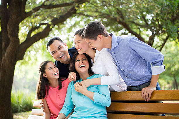 Latin family laughing together outdoors stock photo