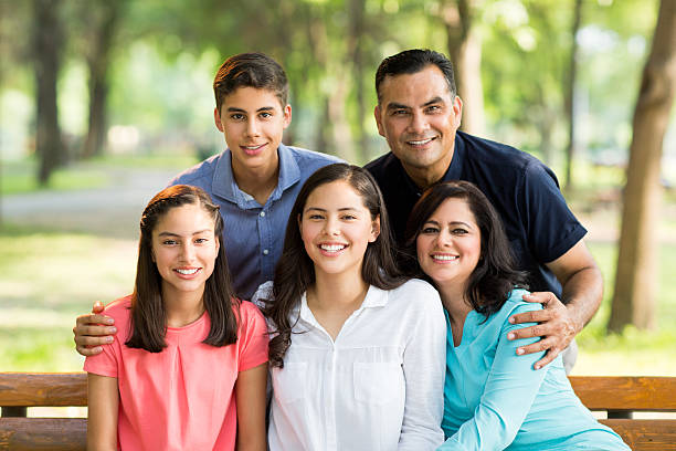 latin family of five embracing and smiling at camera - mexikanische möbel stock-fotos und bilder