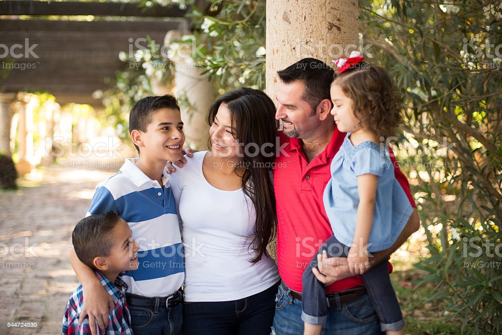 Latin family of five standing and smiling at each other stock photo