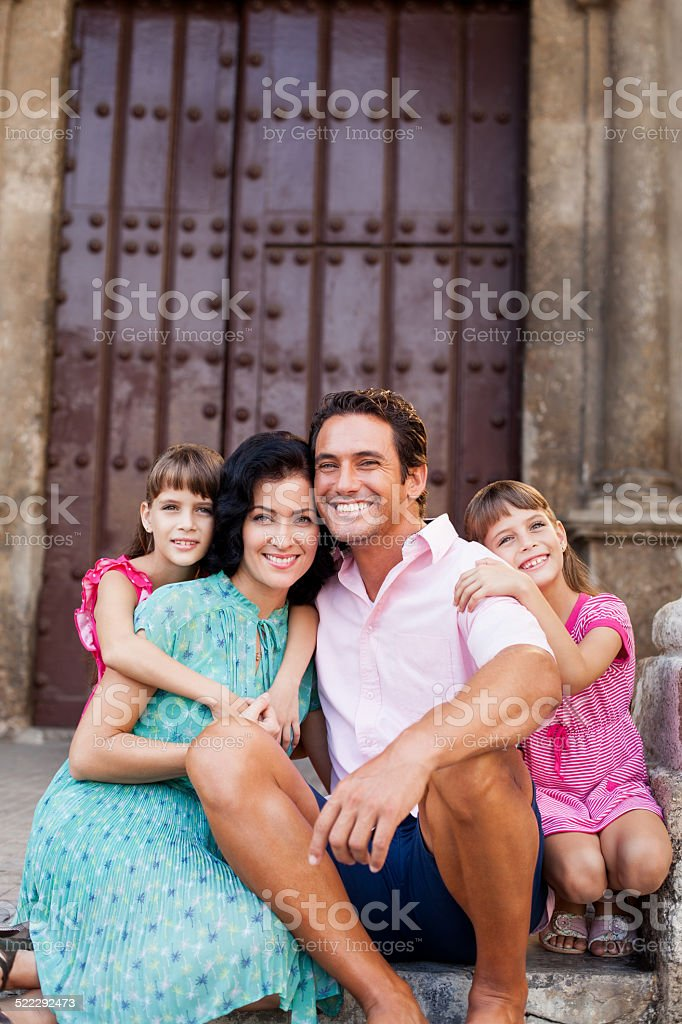 A latin family poses in front of a big door in havana.