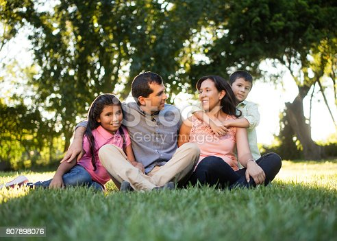 811227514 istock photo Latin family sitting together outdoors 807898076