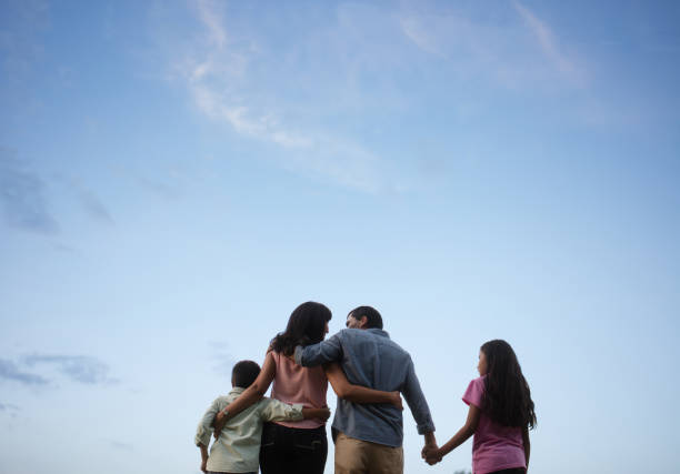 Latin family standing together with sky in background stock photo