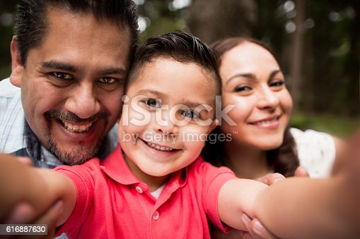 istock Latin family taking a selfie and smiling at camera 616887630