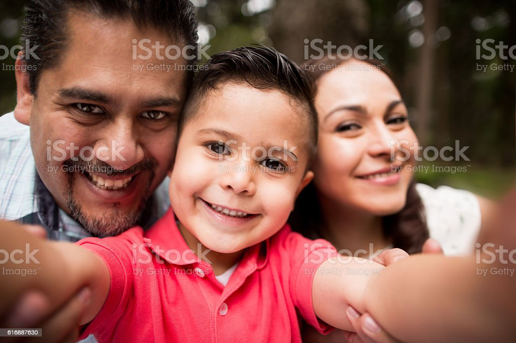 Latin family taking a selfie and smiling at camera stock photo
