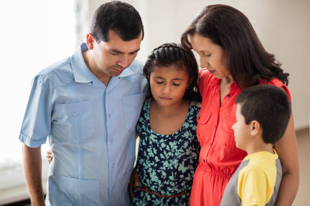 latin family with two children standing and praying together - man face down stock pictures, royalty-free photos & images