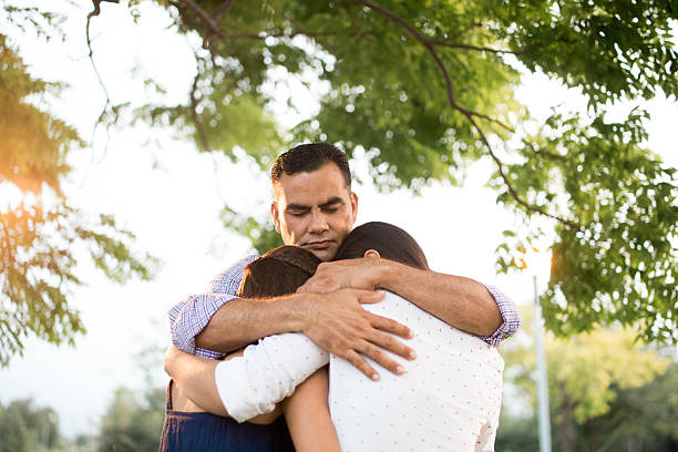Latin father and daughters embracing in circle A latin father embracing his daughters in circle in a horizontal waist up shot outdoors. face down stock pictures, royalty-free photos & images