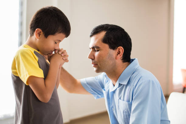 Latin father and son praying face to face stock photo