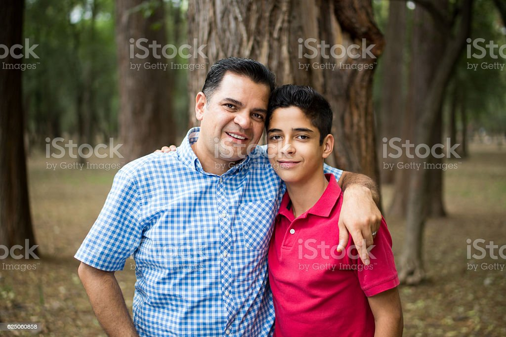 Latin father and teen son standing and smiling at camera - Stock image .