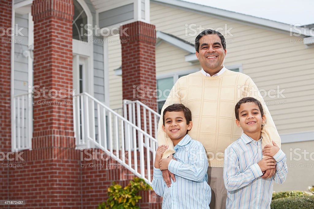 Latin father and twin boys outside townhouse royalty-free stock photo