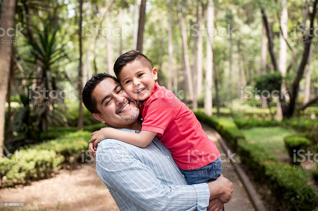 Latin father carrying son and smiling at camera stock photo