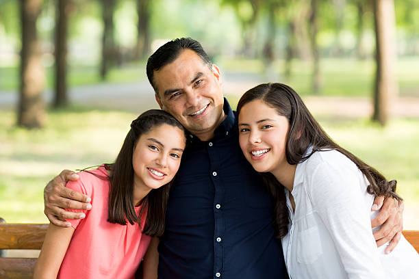 Latin father embracing his daughters and smiling at camera stock photo