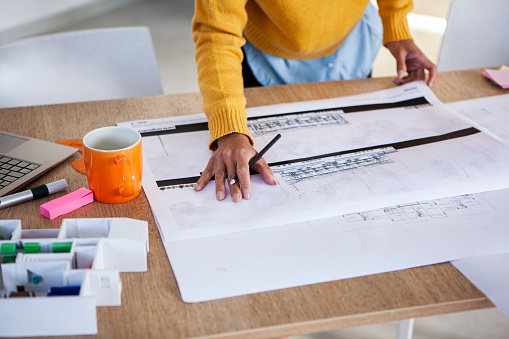 Close-up shot of latin architect woman working on blueprint in studio during day