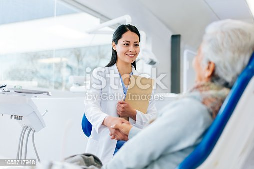 Latin female doctor and senior patient greeting with a handshake in a hospital, looking at each other and smiling.