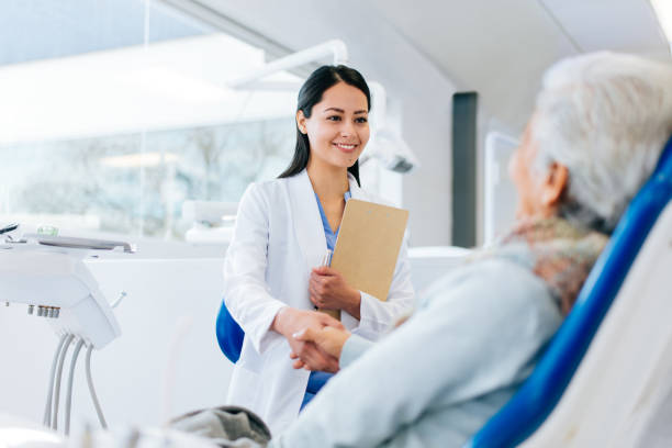 Latin female doctor and patient greeting with handshake Latin female doctor and senior patient greeting with a handshake in a hospital, looking at each other and smiling. dentist stock pictures, royalty-free photos & images