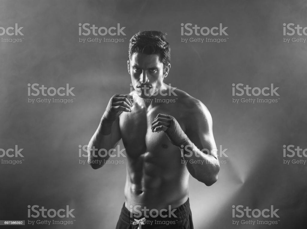 B&W Latin Fighter Posing On A Black Background stock photo